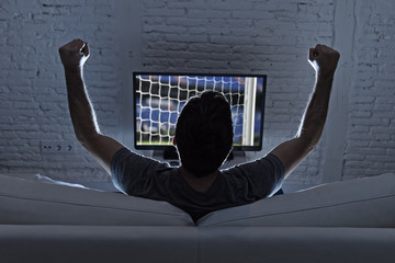 young man home alone watching soccer or football game in television enjoying and celebrating goal