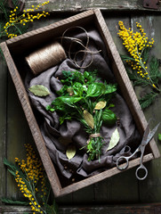 Garni bouquet fresh spring herbs bunch in rustic style with scissors on vintage wooden table background. Top view