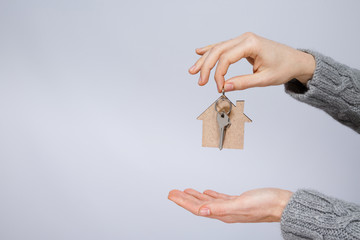 Man in gray sweater holding little wooden house and keys