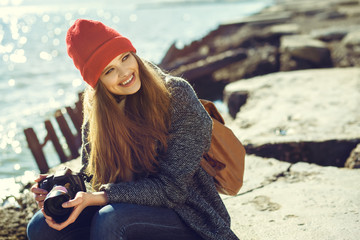 smiling young woman using a camera to take photo. hipster style clothing. Vintage processing. sea shore. smiling girl sitting on the beach