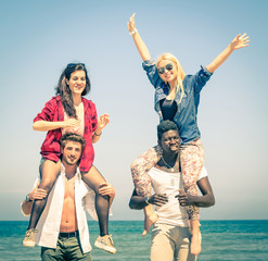 Multiracial best friends at beach having fun with piggyback game - Spring summer concept of multi ethnic friendship against racism - Young people playing together outdoors - Soft vintage filtered look