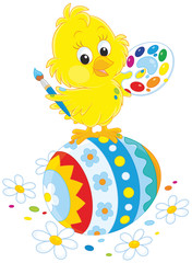 Little yellow chick painted an Easter egg