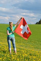 Wall Mural - Girl holding Swiss flag. Emmental, Switzerland