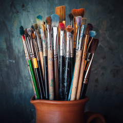 Paintbrushes in a jug from potters clay on dark panting backgrou