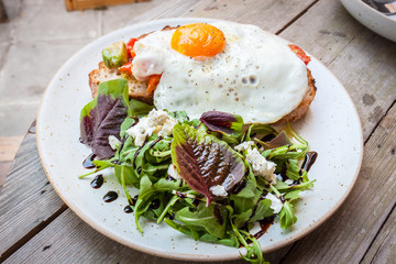 Salad with fried egg  on a wood table