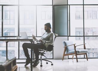 Businessman on modern loft office. Texting message smartphone. Generic design notebook wood table. Horizontal mockup. Film effect.