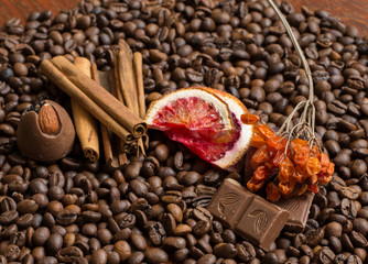 Coffee beans background with citrus  cinnamon, and chocolate