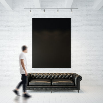 Photo of businessman in gallery. Waching black canvas hanging on the brick wall and vintage classic sofa wood floor. Square, empty mockup. Motion blur