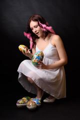 Ung tjej med påskägg och påskfjädrar i håret