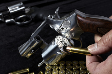 Man loading compact magnum revolver firearm