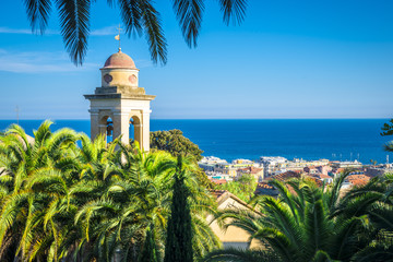 Spoed Foto op Canvas Liguria the belfry and church's roof is hiding behind the palms, sanremo, italy