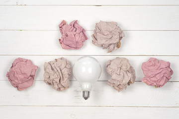 great idea concept with crumpled colorful paper and light bulb on wooden background