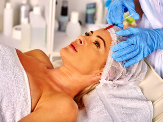 Woman middle-aged in spa salon with beautician.  Female giving injections.