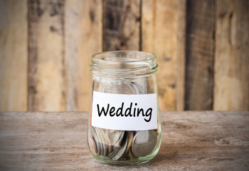 Coins in glass money jar with wedding label, financial concept.