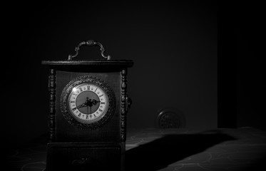 Wooden old vintage clock in a dark room. Spooky abstract scene. Black and white photo.