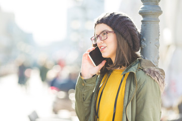 Young modern woman talking on the phone. She is leaning a pillar.