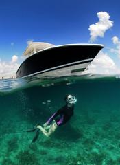 Wall Mural - Underwater image of woman snorkeling near boat