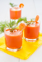 Carrot juice in glasses on yellow napkin