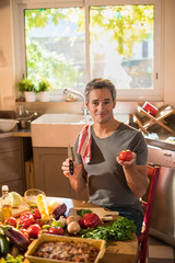 Smiling grey haired man is about to cut a tomato with a knife.