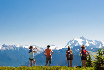 Four women enjoying the view of mountains at the top of their hike on a sunny day.