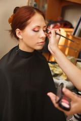 Makeup artist applying make-up on a model.