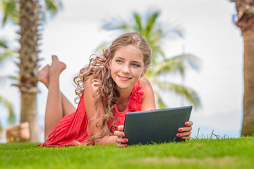 Smiling young girl with digital tablet laying on grass and looking away. Palm trees on background.