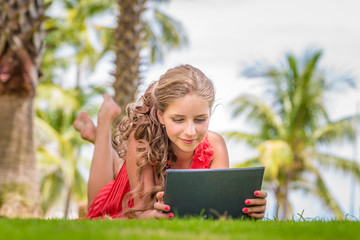 Young girl laying on grass and using digital tablet. Palm trees on background.