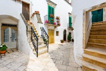 Obraz Locorotondo, Italy. Medieval whitewashed street and houses in small city of Puglia, Apulia, Bari region. - fototapety do salonu