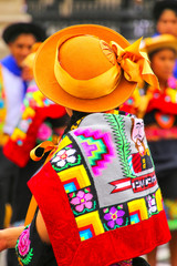Woman wearing traditional hat and back cloth during Festival of