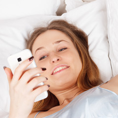 Young woman using smartphone on the bed