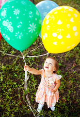 Baby girl 2-3 year old holding balloons outdoors. Birthday party