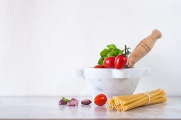 mortaio con pomodori e basilico, accanto pasta e spicchi d'aglio; spazio vuoto