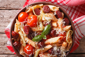 pasta with sausage, leeks, cheese and tomato close up. horizontal top view