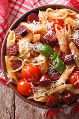 pasta with sausage, leeks, cheese and tomato close up. vertical top view