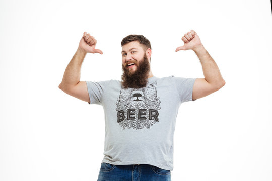 Successful happy bearded man pointing on himself