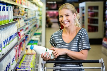 Smiling woman with cart looking at milk bottle