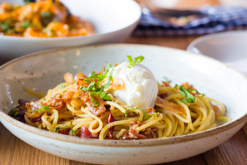 Poached egg on spaghetti with bacon and garlic