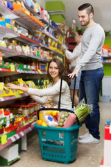 customers standing near shelves with canned goods at shop