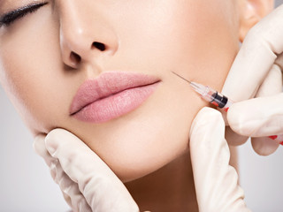 Beautiful woman having injections near lips