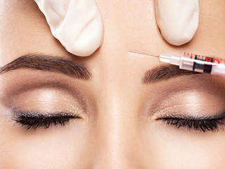 Woman getting injections in forehead