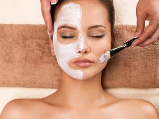 Woman having a facial cosmetic mask at spa salon.