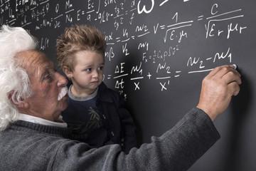 Nonno scienziato che scrive alla lavagna con nipotino in braccio