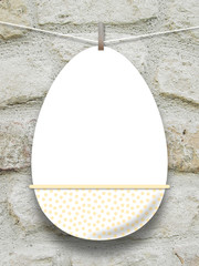 Close-up of one hanged blank Easter egg with peg against grey stone wall background