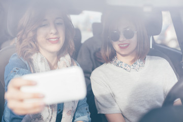 Two beautiful young women making selfie and smiling inside a car