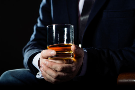 Closeup of serious businessman holding  glass of whiskey illustrate executive privilege concept.