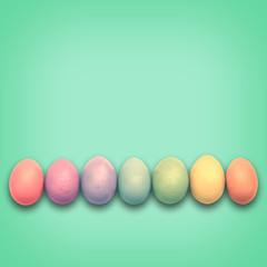 Pastel Easter eggs aligned, green background