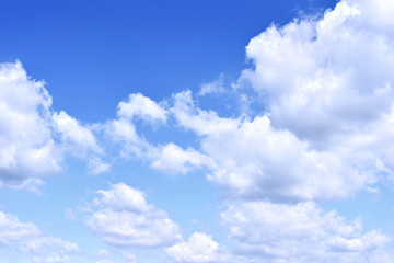 Blue sky with white cumulus clouds. Cloudscape in the sun, good weather with copy space. Nature background with clear blue sky and fluffy clouds.