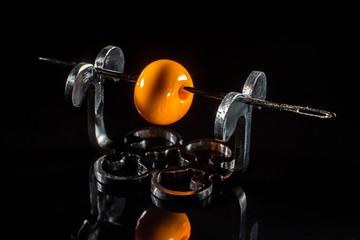 Orange glass bead on stand