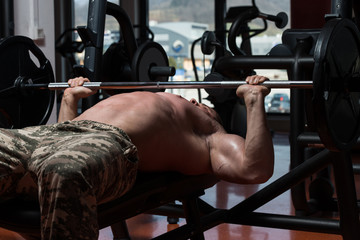 Bodybuilder Exercising Chest With Barbell