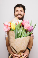 Portrait Handsome young man with beard  and nice bouquet of flowers against white background